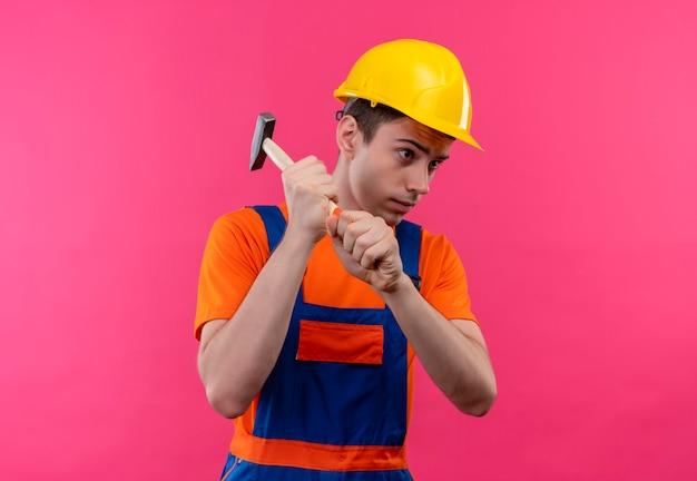 Jonge bouwersmens die bouwuniform en veiligheidshelm dragen houdt een hamer
