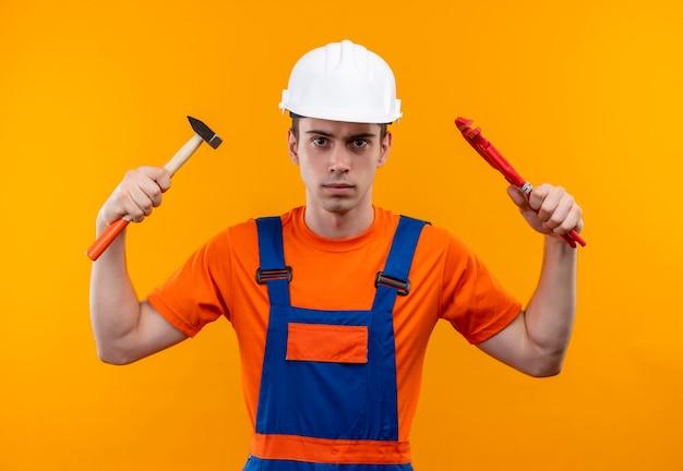 Jonge bouwersmens die bouwuniform en veiligheidshelm dragen houdt een moersleutel en een groeftang