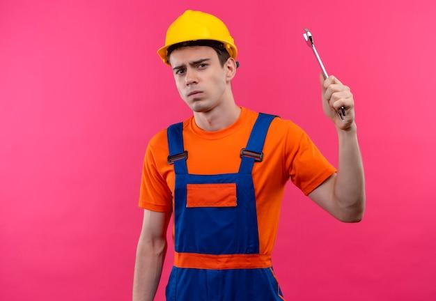 Jonge bouwersmens die bouwuniform en veiligheidshelm dragen houdt een moersleutel