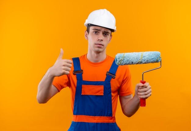 Jonge bouwersmens die bouwuniform en veiligheidshelm dragen houdt een rolborstel en doet gelukkige duimen omhoog
