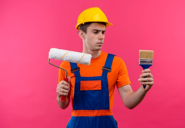 Jonge bouwersmens die bouwuniform en veiligheidshelm dragen houdt een rolborstel en een muurverfborstel