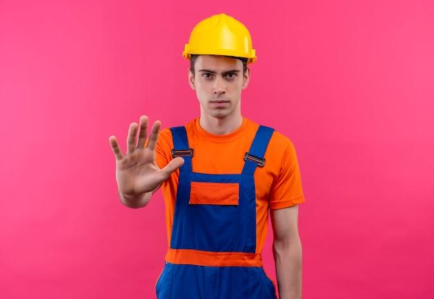 Jonge bouwersmens die bouwuniform en veiligheidshelm dragen houdt shows stop met zijn hand