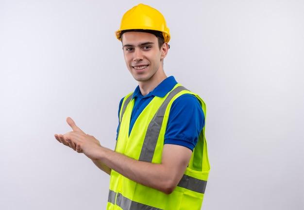 Jonge bouwersmens die bouwuniform en veiligheidshelm dragen juicht toe