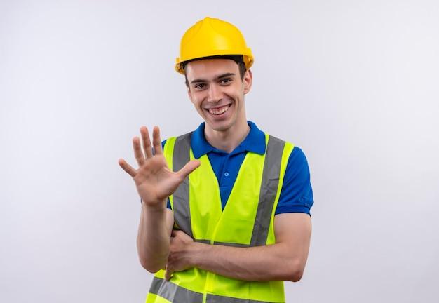 Jonge bouwersmens die bouwuniform en veiligheidshelm dragen toont gelukkig vijf met hand
