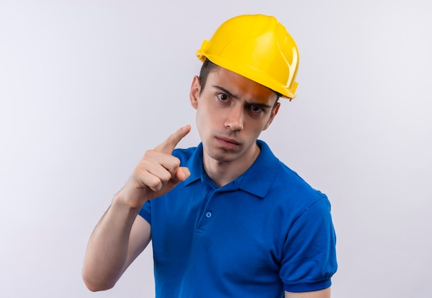 Jonge bouwersmens die bouwuniform en veiligheidshelm dragen, verwijten iemand boos
