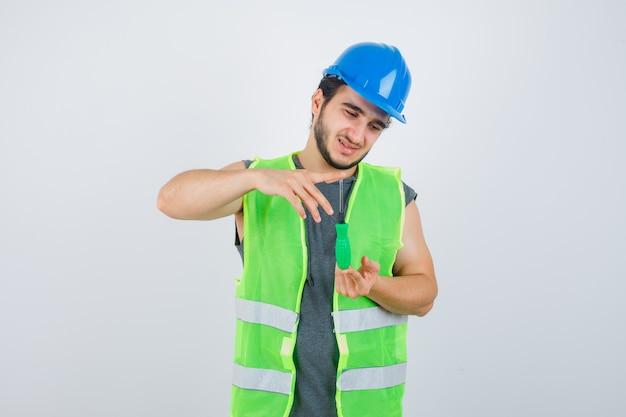Jonge bouwersmens die grootteteken met schroevendraaier in uniform tonen en gelukkig kijken. vooraanzicht.