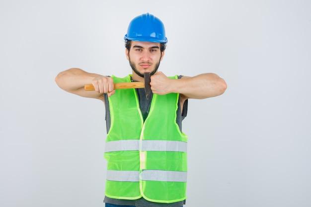 Jonge bouwersmens die hamer houdt terwijl gebalde vuist in uniform werkkleding wordt getoond en er zelfverzekerd uitziet. vooraanzicht.