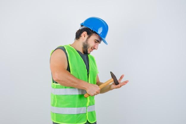 Jonge bouwersmens die hamer op palm in uniform werkkleding slaan en vreugdevol, vooraanzicht kijkt.