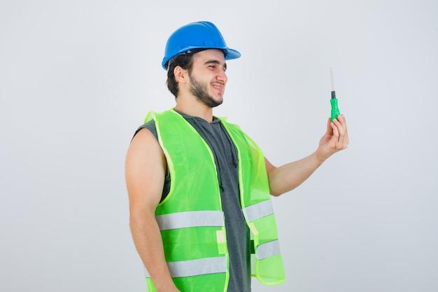 Jonge bouwersmens die schroevendraaier in uniform toont en gelukkig kijkt. vooraanzicht.