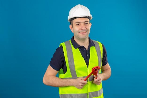 Jonge bouwersmens die witte helm en een geel vest dragen, die moersleutelhulpmiddel met een glimlach op gezicht op geïsoleerd blauw in hand houden
