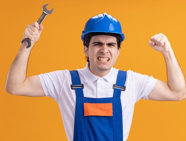 Jonge bouwersmens in bouwuniform en de moersleutel van de veiligheidshelmholding die handen boos en ontevreden opheft die zich over oranje muur bevinden