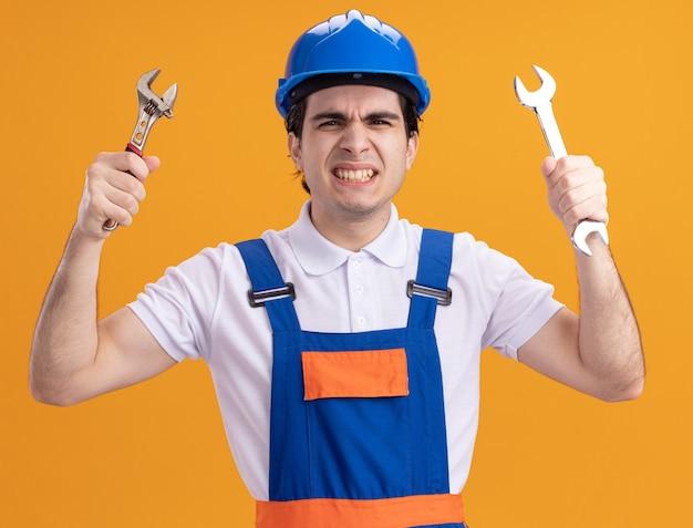 Jonge bouwersmens in bouwuniform en de moersleutels van de veiligheidshelmholding die voorzijde met boos gezicht bekijken dat zich over oranje muur bevindt