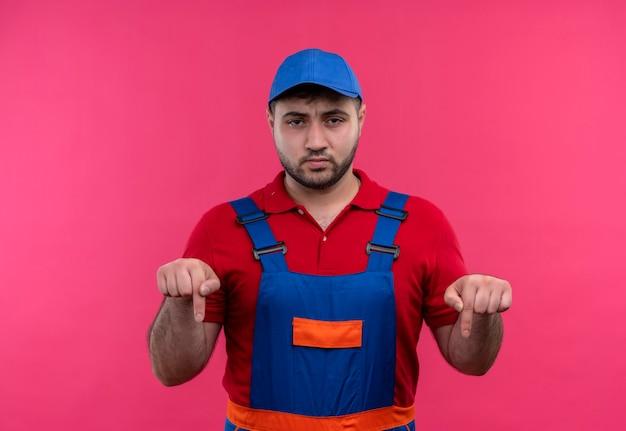 Jonge bouwersmens in bouwuniform en glb die met vingers neer met fronsend gezicht wijzen