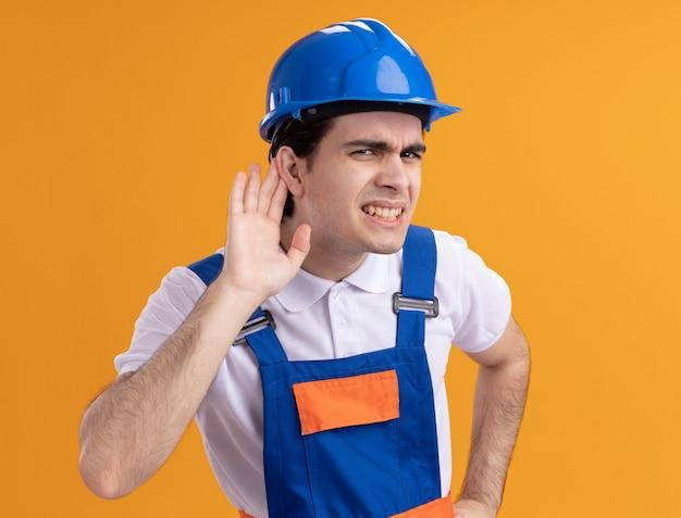Jonge bouwersmens in bouwuniform en veiligheidshelm die aan voorzijde met hand over oor kijken die naar roddels proberen te luisteren die verward over oranje muur staan