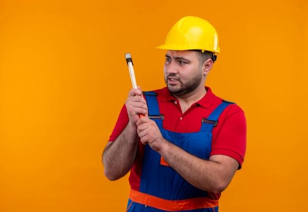 Jonge bouwersmens in bouwuniform en veiligheidshelm die een hamer met boos gezicht slingeren