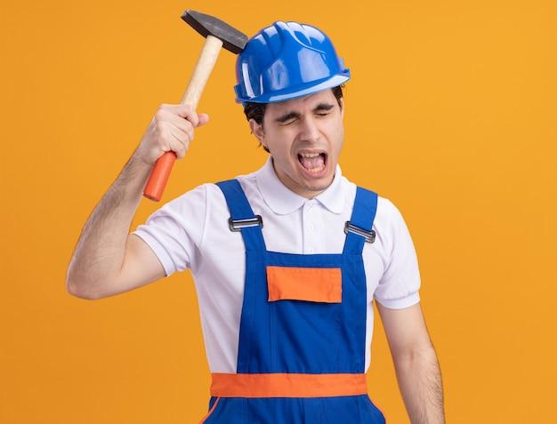Jonge bouwersmens in bouwuniform en veiligheidshelm die eigen hoofd met hamer slaan met geïrriteerde uitdrukking die zich over oranje muur bevindt