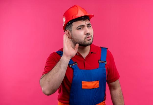 Jonge bouwersmens in bouwuniform en veiligheidshelm die hand dichtbij oor houden die yo proberen te luisteren