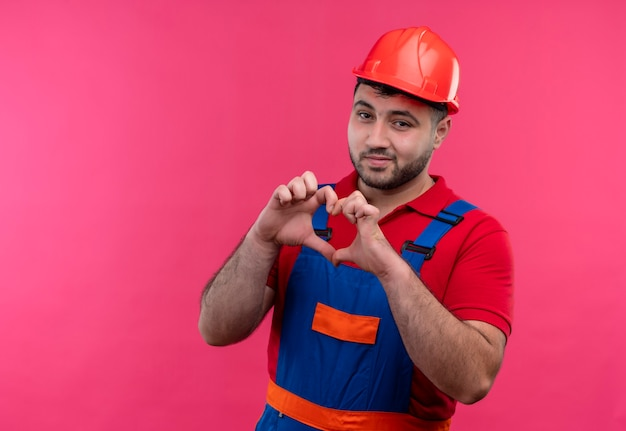 Jonge bouwersmens in bouwuniform en veiligheidshelm die hartgebaar met vingers over borst het glimlachen maken