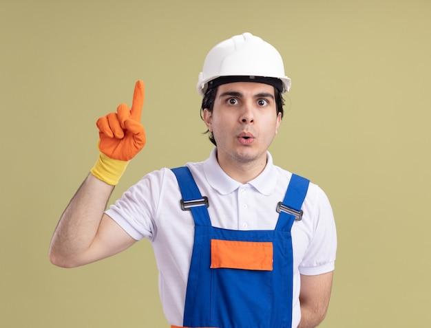 Jonge bouwersmens in bouwuniform en veiligheidshelm die in rubberhandschoenen voorzijde bekijken verbaasd tonen wijsvinger die nieuw idee hebben die zich over groene muur bevinden