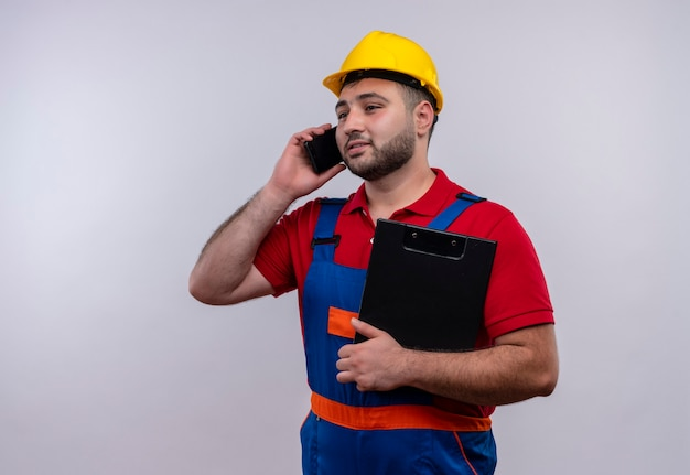 Jonge bouwersmens in bouwuniform en veiligheidshelm die klembord glimlachen terwijl het spreken op mobiele telefoon