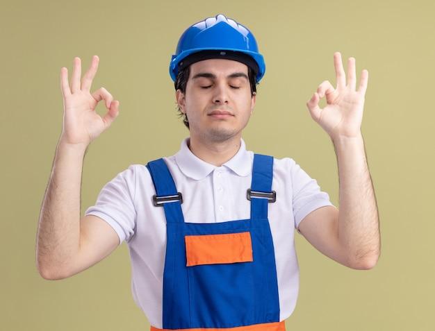 Jonge bouwersmens in bouwuniform en veiligheidshelm die meditatiegebaar met vingers met gesloten ogen maken die zich over groene muur bevinden