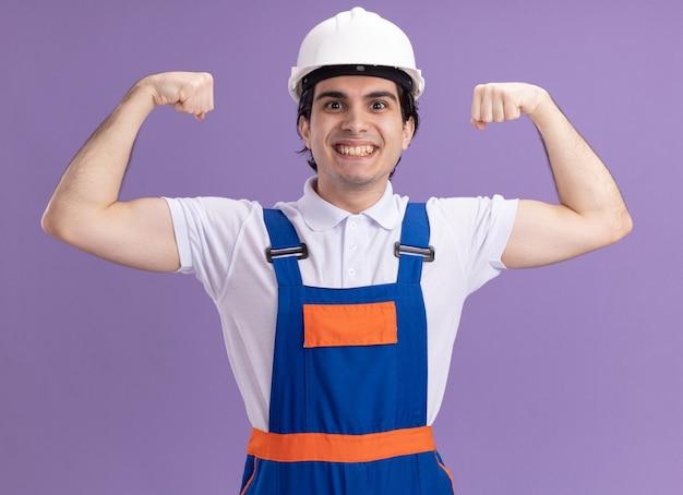 Jonge bouwersmens in bouwuniform en veiligheidshelm die met gelukkig gezicht glimlachen die vuisten opheffen die zich als een winnaar stellen die zich over purpere muur bevindt