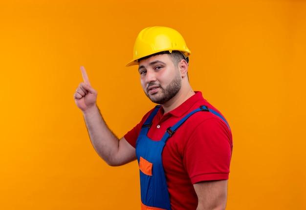 Jonge bouwersmens in bouwuniform en veiligheidshelm die met wijsvinger omhoog wijzen die op zoek slim en zelfverzekerd gericht op taak kijken