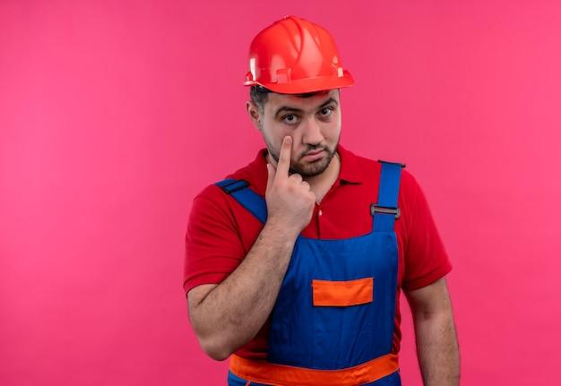 Jonge bouwersmens in bouwuniform en veiligheidshelm die met wijsvinger richten naar oog kijken naar je gebaar