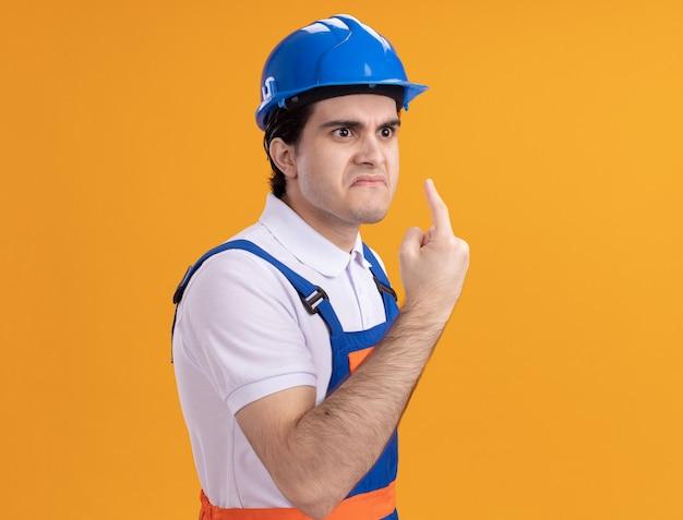 Jonge bouwersmens in bouwuniform en veiligheidshelm die opzij met boos gezicht kijken die wijsvingerwaarschuwing tonen die zich over oranje muur bevinden