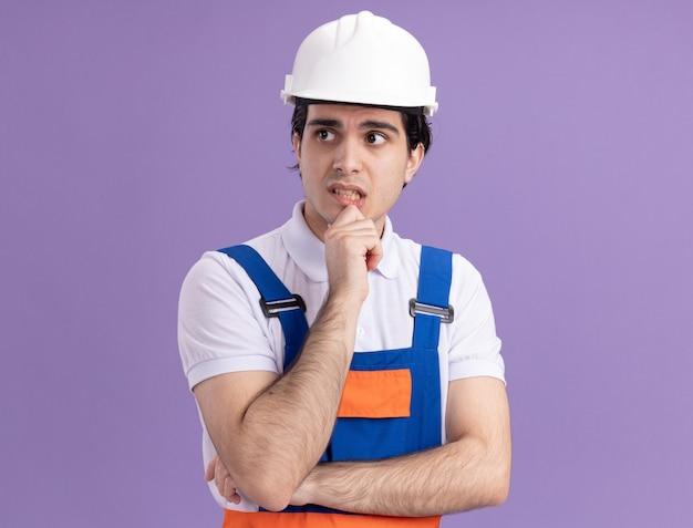 Jonge bouwersmens in bouwuniform en veiligheidshelm die opzij met peinzende uitdrukking denken die zich over purpere muur bevinden Gratis Foto