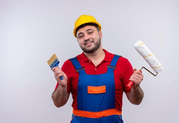 Jonge bouwersmens in bouwuniform en veiligheidshelm die pintroller en borstel vrolijk glimlachen