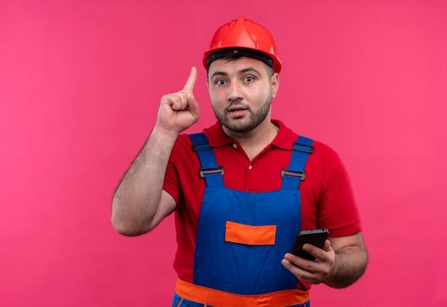 Jonge bouwersmens in bouwuniform en veiligheidshelm die smartphone tonen die wijsvinger tonen die zich eraan herinneren niet te vergeten