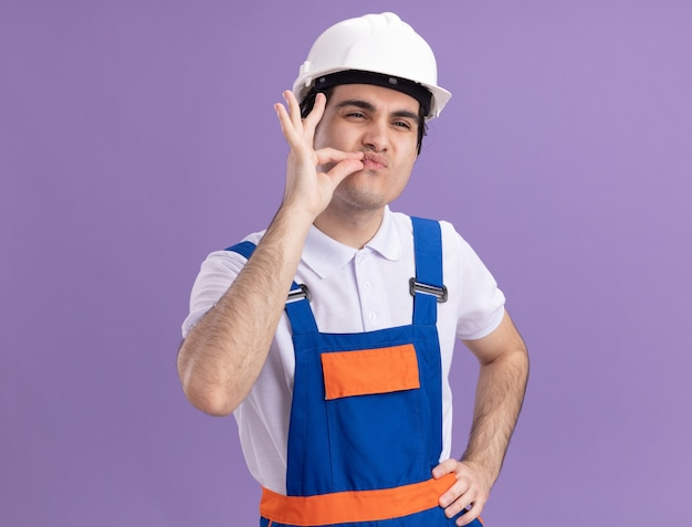 Jonge bouwersmens in bouwuniform en veiligheidshelm die stilte gebaar maken met vingers zoals het sluiten van mond met een ritssluiting die zich over paarse muur bevindt