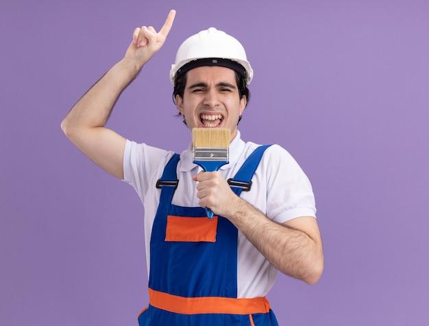 Jonge bouwersmens in bouwuniform en veiligheidshelm die verfborstel houden die aan het gelukkige en vreugdevolle status over purpere muur zingen