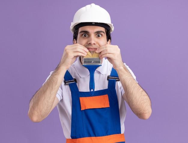Jonge bouwersmens in bouwuniform en veiligheidshelm die verfborstel houden die baard imiteert die pret op het werk hebben die zich over purpere muur bevinden