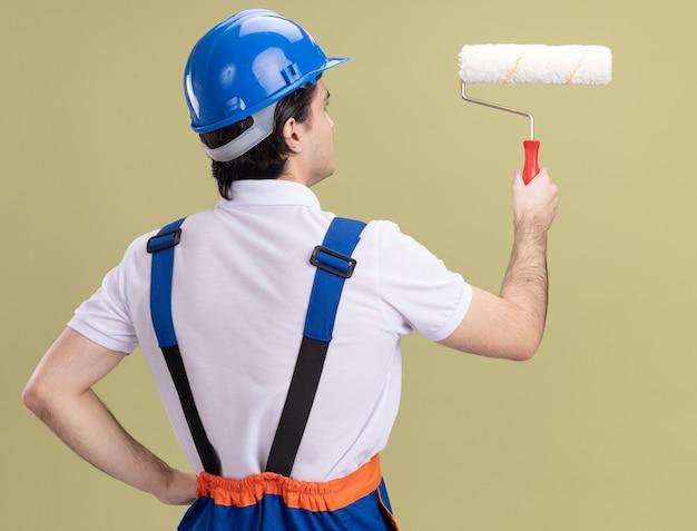 Jonge bouwersmens in bouwuniform en veiligheidshelm die verfroller houden die zich met zijn rug over groene muur bevinden