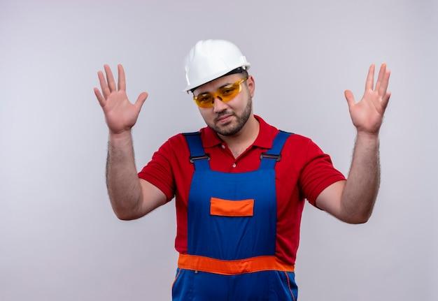 Jonge bouwersmens in bouwuniform en veiligheidshelm die verward en onzeker kijken die schouderophalend geen antwoord hebben