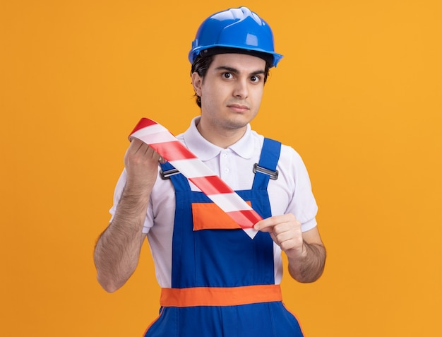 Jonge bouwersmens in bouwuniform en veiligheidshelm die voorzichtigheidsband houden die voorzijde met ernstige zelfverzekerde uitdrukking bekijken die zich over oranje muur bevinden