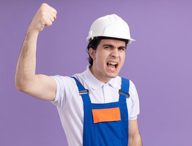 Jonge bouwersmens in bouwuniform en veiligheidshelm die voorzijde bekijken die met boos gezicht schreeuwen die vuist opheffen die zich over purpere muur bevinden