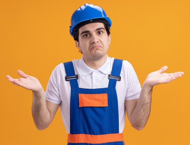 Jonge bouwersmens in bouwuniform en veiligheidshelm die voorzijde verward en onzeker bekijken schouderophalend die zich over oranje muur bevinden