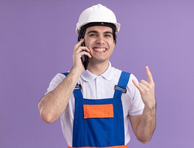 Jonge bouwersmens in bouwuniform en veiligheidshelm die vrolijk glimlachen makend rotssymbool die op mobiele telefoon spreken die zich over purpere muur bevinden