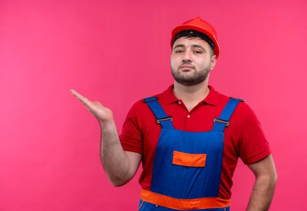 Jonge bouwersmens in bouwuniform en veiligheidshelm die zelfverzekerd exemplaarruimte met arm kijken oh zijn hand