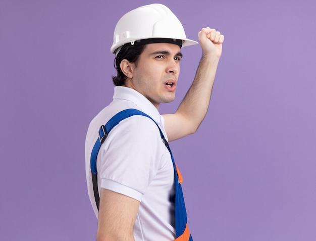 Jonge bouwersmens in bouwuniform en veiligheidshelm die zich met zijn rug bevinden die vuist over purpere muur opheffen