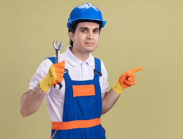 Jonge bouwersmens in bouwuniform en veiligheidshelm in rubberhandschoenen die moersleutel houden die aan voorzijde met ernstig gezicht kijkt dat met wijsvinger naar de zij wijst die zich over groene muur bevindt