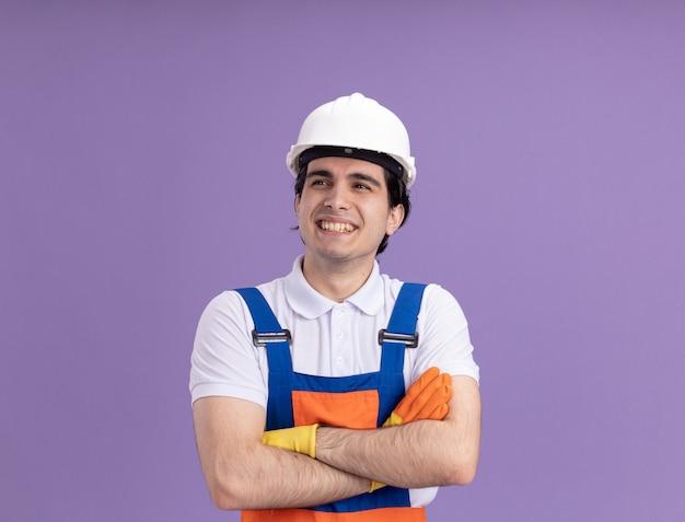 Jonge bouwersmens in bouwuniform en veiligheidshelm in rubberhandschoenen die opzij glimlachend vrolijk met gekruiste wapens kijken die zich over purpere muur bevinden