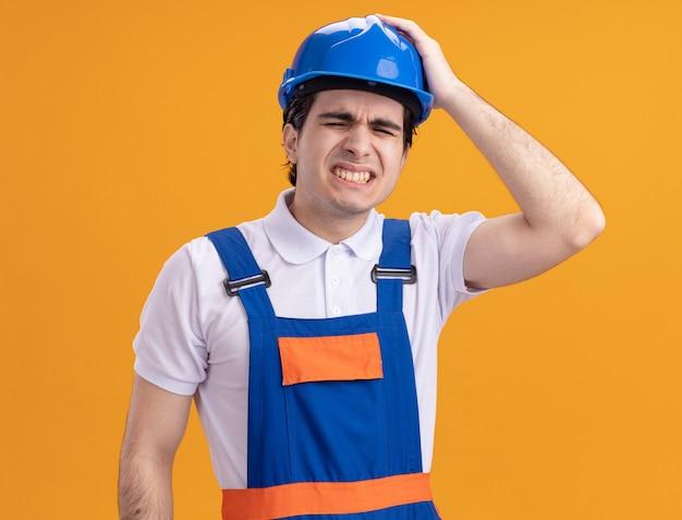 Jonge bouwersmens in bouwuniform en veiligheidshelm kijkt verward en erg bezorgd met hand op zijn hoofd wegens fout die over oranje muur staat