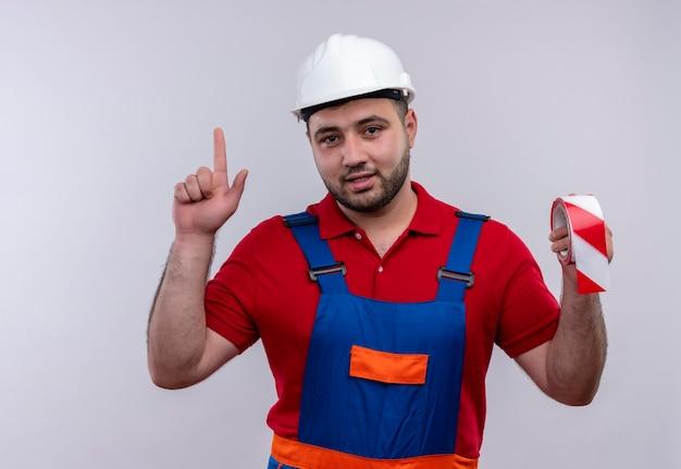 Jonge bouwersmens in bouwuniform en veiligheidshelm met plakband op zoek zelfverzekerd wijzend met wijsvinger omhoog
