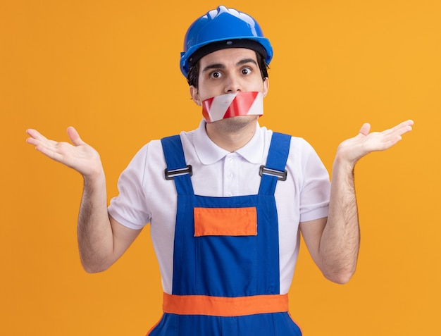 Jonge bouwersmens in bouwuniform en veiligheidshelm met tape rond de mond op zoek verward schouderophalend staande over oranje muur