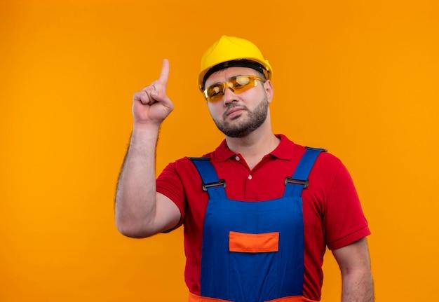 Jonge bouwersmens in bouwuniform en veiligheidshelm op zoek zelfverzekerd wijzend met wijsvinger omhoog over oranje achtergrond