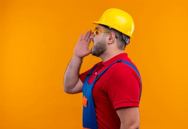 Jonge bouwersmens in bouwuniform en veiligheidshelm zijwaarts schreeuwen of iemand met hand dichtbij mond roepen